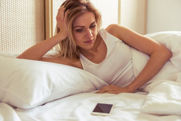 54222532 - side view of beautiful girl looking at a mobile phone while lying in bed